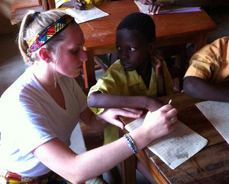 Volunteer helping students with schoolwork.