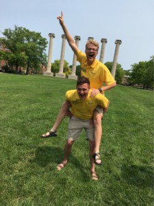 Joshua Varnon and a friend goof around on Francis Quadrangle in front of the Columns.