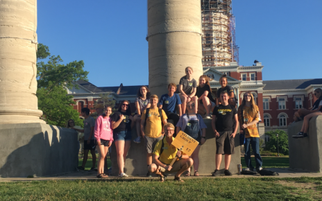 A student group poses in front of the Columns on the University of Missouri's campus.