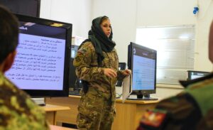 Mariah Best stands in front of a room and answers a question from an Afghan National Army soldier.