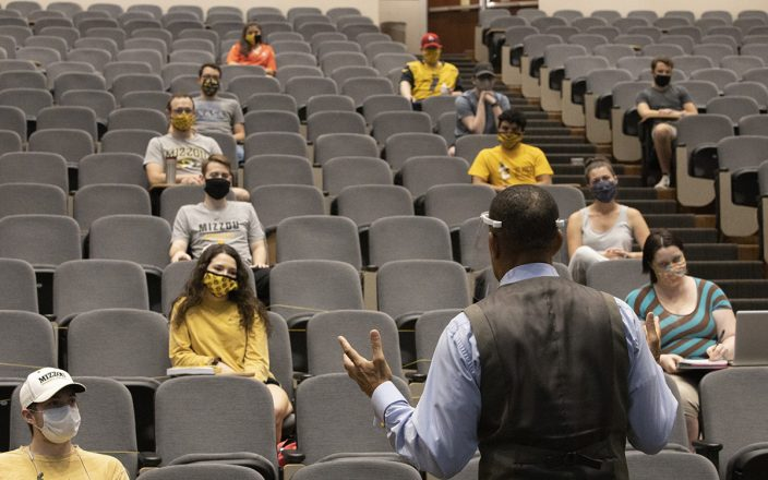 Students sit socially distanced in an MU lecture hall