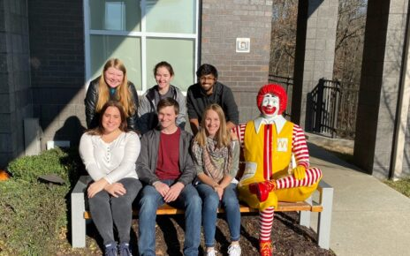 Stamps Scholars sit on bench with statue of Ronald McDonald