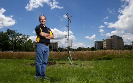 Eric Aldrich stands beside the Sanborn Field weather station on the MU campus.